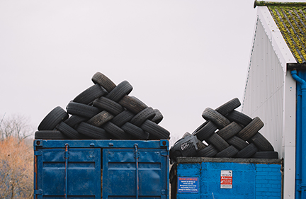 stack of tires in two blue bins