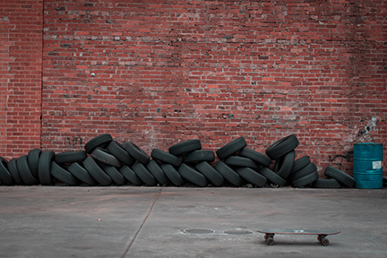 tires stored against an exposed brick wall