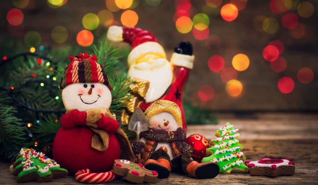 snowman and santa claus beneath the christmas tree