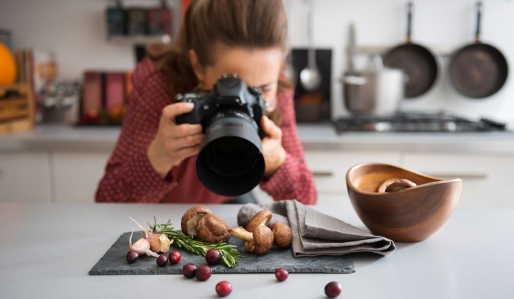 a girl taking pictures of garlic, mushroom and berries