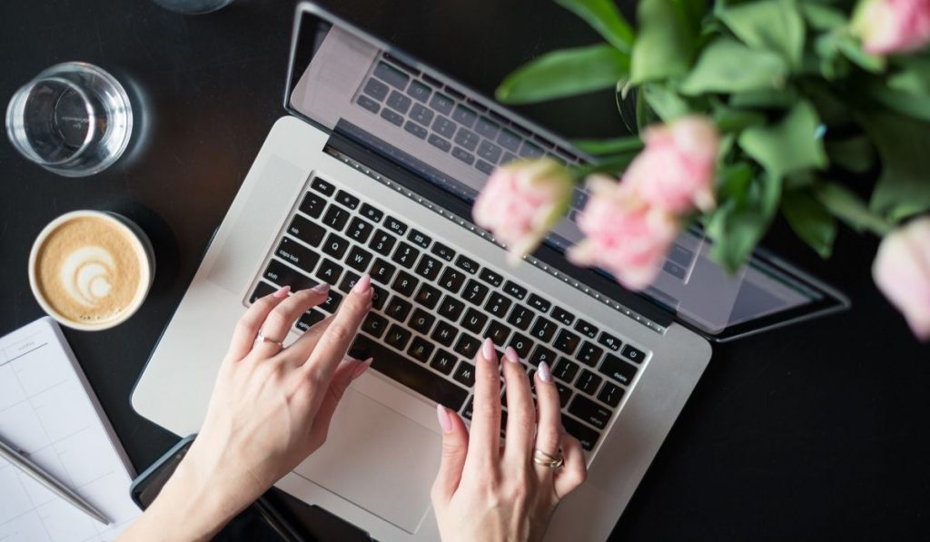 a woman typing on the laptop